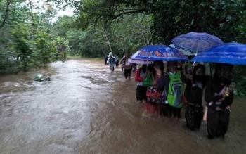 Beberapa warga Muara Teweh, Kabupaten Barito Utara nekad melintasi luapan banjir