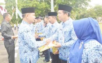 Bupati Kapuas Ben Brahim S Bahat menyerahkan piagam penghargaan kepada PNS berprestasi seusai upacara peringatan HUT ke-46 Korpri, Kamis (30/11/2017).