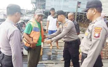 Kapolsek KPM Iptu Irfan Ali Reja bersama sejumlah anggotanya saat membagikan pelampung kepada seorang motoris kelotok di dermaga Kota Sampit, Jumat (1/12/2017).