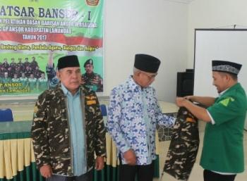 Ketua PC GP Ansor Lamandau Salman Azzuhri memakaikan jaket khas Banser NU kepada Tommy Hermal Ibrahim dan Arsyadi Madiah, Jumat (1/12/2017).