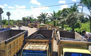 Ratusan truk berjejer di tepi jalan saat menggelar aksi, Senin (4/12/2017).