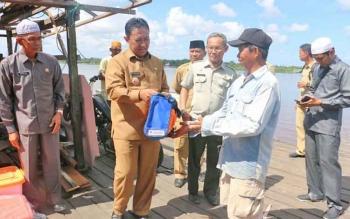 Bupati Pulang Pisau Edy Pratowo saat menyerahkan bantuan kepada korban angin kencang di wilayah Kecamatan Kahayan Hilir.