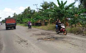Sejumlah pengendara saat menghindari lubang menganga yang berada di Desa Lampuyang, Kecamatan Teluk Sampit.