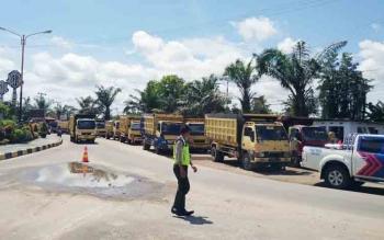Sejumlah polisi sedang melakukan pengamanan terhadap aksi demo para sopir truk galian c di Jalan Jenderal Sudirman Km 3, Senin (4/12/2017).