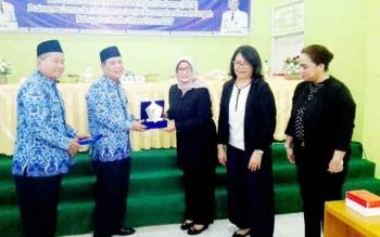 Sekda Barito Utara, Jainal Abidin didampingi Kepala Dinas Kesehatan H Robansyah menyerahkan plakat kepada tim survei akrediitasi puskesmas, Senin (4/12/2017)