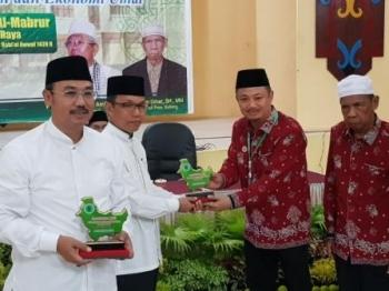 Panitia Rakorda sekaligus Bendahara MUI Kalteng memberi cindera mata kepada Plt Sekda Kalteng di pembukaan Rakorda MUI Regional Kalimantan tadi malam