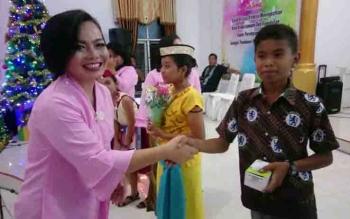 Ketua Komisi Pelayanan Perempuan (KPPer) Resort Gereja Kalimantan Evangelist (GKE) Kuala Kurun, Warsinie Edyson Kenting menyerahkan tali asih.