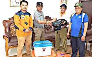 Kepala Bidang Kesiapsiagaan dan Pencegahan BPBD Kapuas, Jendrawan menyerahkan bantuan kepada Kepala Desa Mampai, Abdullah.