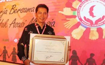Bupati Barito Utara H Nadalsyah saat menerima penghargaan yang diserahkan langsung oleh Menkum HAM Yasonna Laoly di Hotel Sunan Solo, Minggu (10/12/2017)