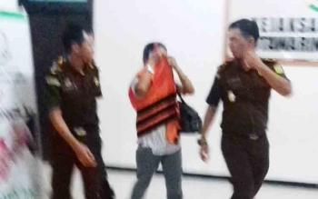 Lilis Suryani menutup wajahnya dengan rompi orange saat ditahan jaksa.