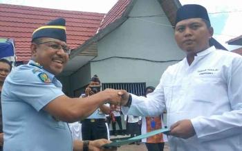 Kepala Divisi Pemasyarakatan Kanwil Kemenkum HAM Kalteng Anthonius M Ayorbaba (kiri) memberikan surat remisi kepada perwakilan warga binaan di Lapas Kelas IIB Sampit, Rabu (13/12/2017).