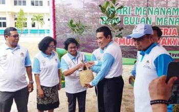 Asisten III I Kethut Widhie Wirawan menyerahkan pohon ke sejumlah pihak dalam rangka HMPI dan Bulan Menanam Nasional tingkat Provinsi Kalteng, Kamis (14/12/2017)