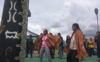 terlihat wanita tetua adat bersama penari lainnya sedang menari manasai mengelilingi tempat persembahan roh suci
