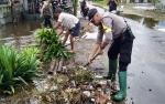 Bhabinkamtibmas Kelurahan Menteng Ikut Bersihkan Drainase Tersumbat Sampah