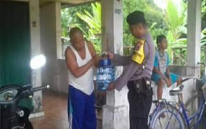 Anggota Polsek Basarang Bantu Perangkat Desa Lunuk Ramba Bagikan Galon untuk Cuci Tangan
