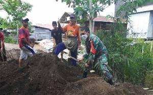 Babinsa Pahandut Sebrang Ajak Warga Gotong Royong Timbun Jalan Berlubang
