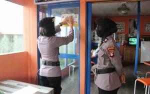 Polwan Polres Kapuas Pasang Stiker Kawasan Wajib Masker di Tempat Umum