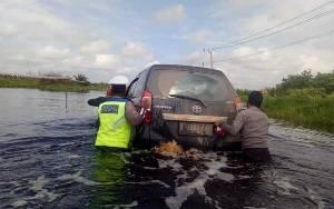 Polantas Kobar Bantu Dorong Mobil Lintasi Jalan Tergenang Banjir