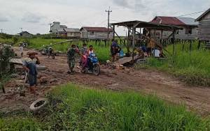 Babinsa Koramil 1016-01 Pahandut Bersama Warga Perbaiki Jalan Berlubang
